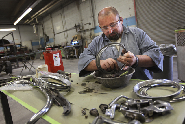 An inmate worker polishes chrome accessories while participating in the car restoration program, operated through Silver State Industries, at the Southern Desert Correctional Center near Indian Sp ...
