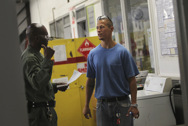 An inmate worker in the car restoration program, right, talks with a correctional officer at the Southern Desert Correctional Center near Indian Springs on Sept. 12, 2013. (Jason Bean/Las Vegas Re ...