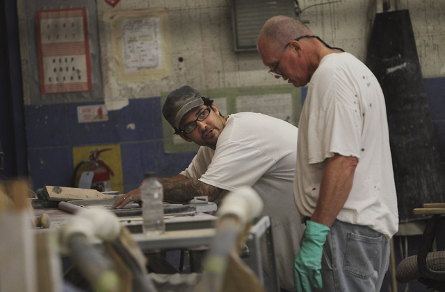 Inmate workers talk over a project while participating in the car restoration program, operated through Silver State Industries, at the Southern Desert Correctional Center near Indian Springs on S ...