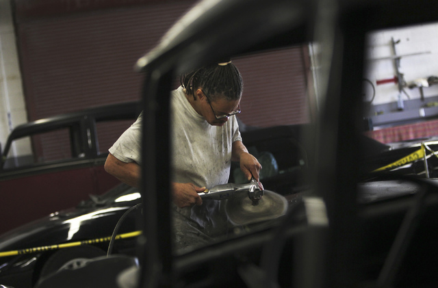 An inmate worker buffs a hood panel while participating in the car restoration program, operated through Silver State Industries, at the Southern Desert Correctional Center near Indian Springs on  ...