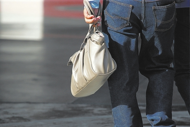 Las Vegas Review-Journal A man holds his wife's purse as they walk outside of the Planet Hollywood hotel-casino off of Las Vegas Boulevard on Friday, Aug. 30, 2013. (Chase Stevens/Las Vegas  ...