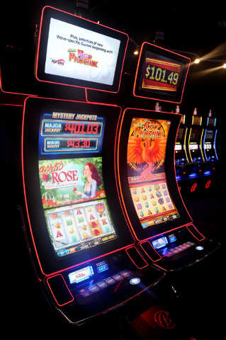 Wild Rose, left, and Red Phoenix slot machines are seen on display inside a showroom at Bally Technologies in Las Vegas Thursday, Sep. 12, 2013. These machines feature a curved design. (David Clev ...