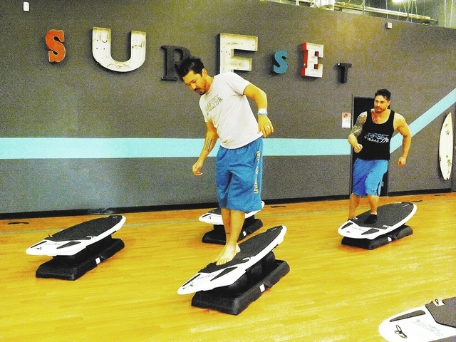 Business owners Jason Laricchia, left, and Jason Santiago demonstrate exercises on modified surfboards on Sept. 10, 2013, at SURFSET Las Vegas, 8665 W. Flamingo Road, No. 126, in Las Vegas. (Caitl ...