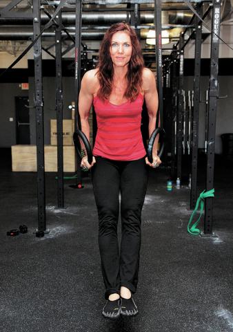 Trainer Laura Salcedo demonstrates the finishing position for the dip exercise on Wednesday, Sep. 4, 2013. (Justin Yurkanin/Las Vegas Review-Journal)