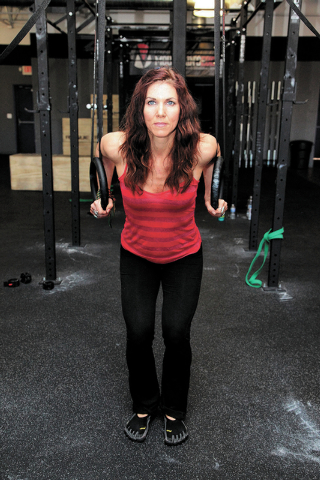 Trainer Laura Salcedo demonstrates the starting position for the dip exercise on Wednesday, Sep. 4, 2013. (Justin Yurkanin/Las Vegas Review-Journal)