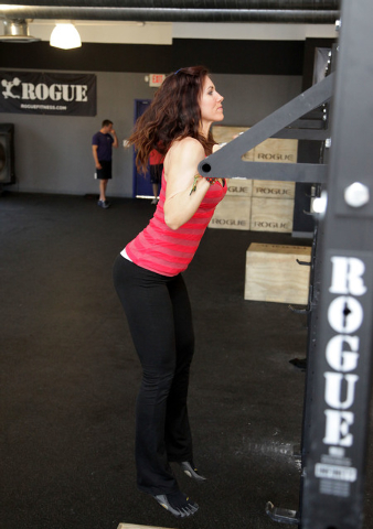 Trainer Laura Salcedo demonstrates the finishing position for the jumping pull-up exercise on Wednesday, Sep. 4, 2013. (Justin Yurkanin/Las Vegas Review-Journal)