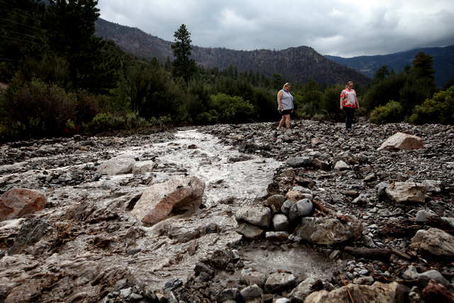 Samantha Dukart, left, and daughter Kaytlyn (cq) walk through runoff on Mount Charleston after heavy rains Sunday, Sep. 1, 2013. The Las Vegas pair were visiting the mountain to see the effects of ...