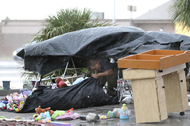 A man who declined to give his name tries to protect the items he was selling at his roadside stand during a downpour on East Lake Mead Boulevard near North Nellis Boulevard Monday. (K.M. Cannon/L ...