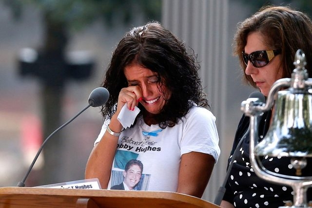 A woman wipers her eyes after reading the name of her brother, Bobby Hughes, as friends and relatives of the victims of the 9/11 terrorist attacks gather at the National September 11 Memorial at t ...