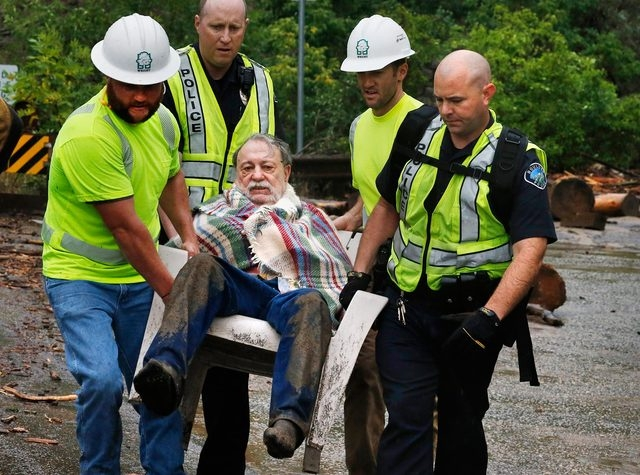Will Pitner is rescued by emergency workers Friday after a night trapped sheltering outside on high ground above his home as it filled with floodwaters at the base of Boulder Canyon, Colo. Rescuer ...