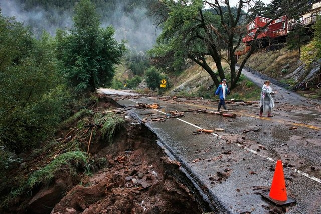 Brother and sister Patrick Tinsley and Mary Kerns on Friday walk into Boulder, Colo., from their mountain community Magnolia, where road access is shut off by debris from days of record rain and f ...