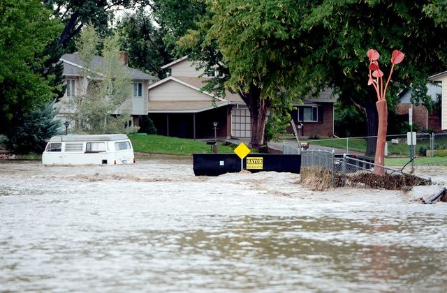 Lefthand Creek floods a street Friday in Longmont, Colo. Thousands of people in Colorado were ordered to evacuate as water rose to dangerous levels amid a storm system that has been dropping rain  ...