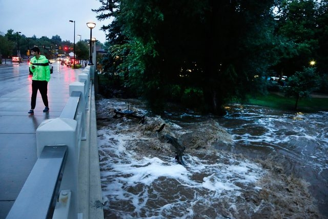 A man walks past dangerously high Boulder Creek Thursday after overnight flash flooding in downtown Boulder, Colo. Flash flooding in Colorado has left two people dead and the widespread high water ...