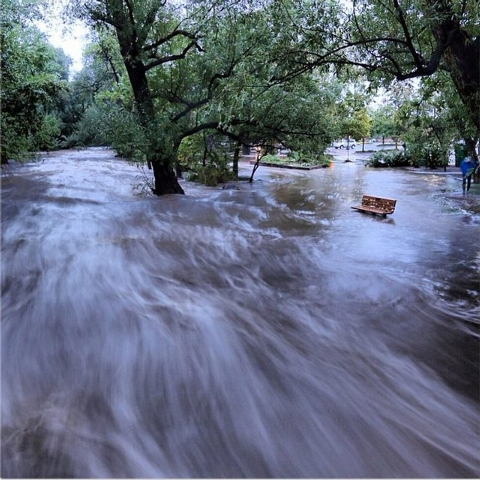 In this image made with a slow shutter speed that blurred the rushing water, flood waters course through a small park in Boulder, Colo., Thursday morning. Heavy rains and scarring from recent wild ...