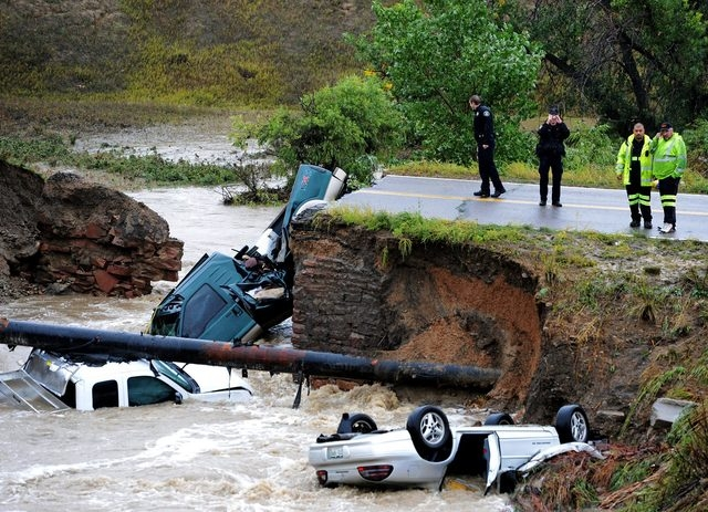 Officials investigate the scene of a road collapse at Highway 287 and Dillon near Broomfield and Lafayette, Colo., that sent three vehicles into the water after flash flooding on Thursday. The Nat ...