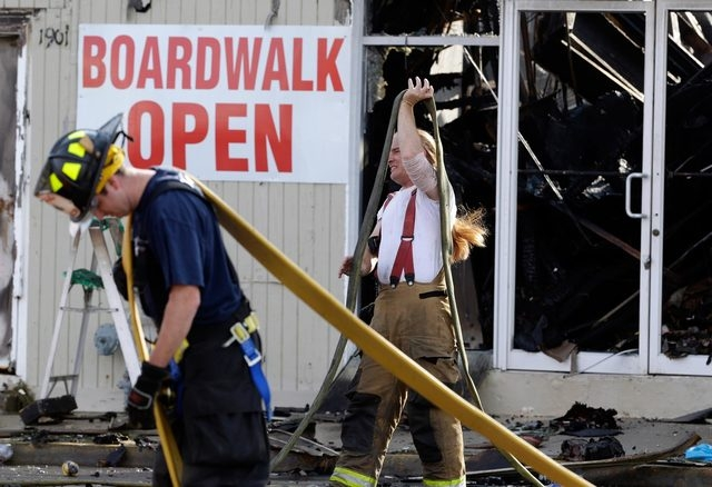 Firefighters arrange hoses Friday morning after a massive fire burned a large portion of the Seaside Park boardwalk in Seaside Park, N.J. The fire hit the recently repaired boardwalk, which was da ...
