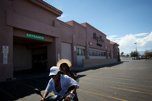 A pair rides a motor scooter past a Buy Low grocery store in Las Vegas Wednesday, Sep. 4, 2013. More popular grocery stores left standing in the West side, like Marios and Buy Low, located in the  ...