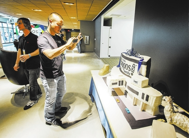 Jeff Scheid/Las Vegas Review-Journal Tony Hsieh, Zappos CEO, takes a photo of a cake in the shape of the company's headquarters at 400 Stewart Ave. Zappos opened its new headquarters Monday  ...