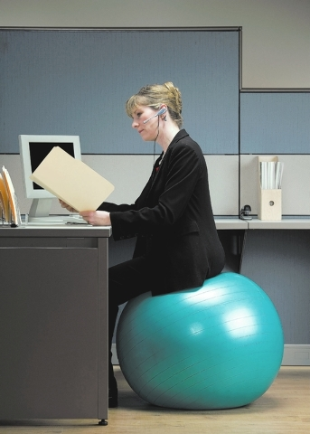 Businesswoman in headset looking at file folder while sitting on