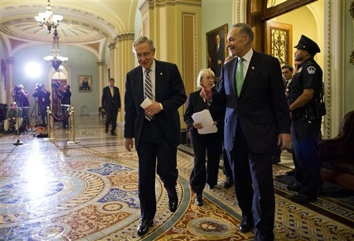Senate Majority Leader Sen. Harry Reid, D-Nev., left, walks off the Senate floor with Sen. Chuck Schumer, D-N.Y., after voting to avoid a financial default and reopen the government after a 16-day ...
