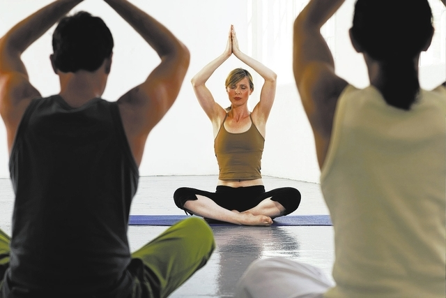 Yoga teacher at front of class, hands in prayer position above head