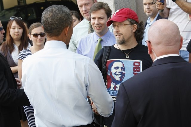 U.S. President Barack Obama (L) greets greets a man in an Obama t-shirt after he and Vice President Joe Biden (not pictured) bought lunch at a sandwich shop near the White House in Washington, Oct ...