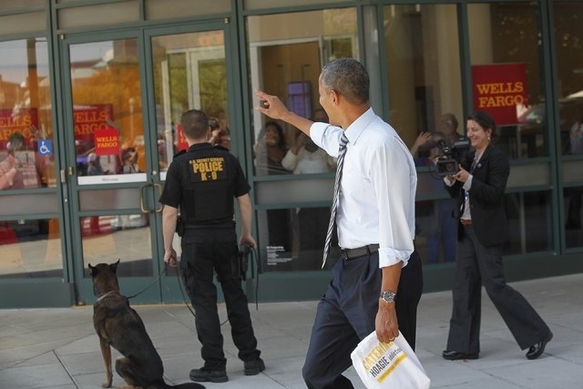 U.S. President Barack Obama waves at people in a bank vestibule after he and Vice President Joe Biden (not pictured) bought lunch at a sandwich shop near the White House in Washington, October 4,  ...