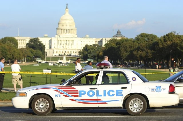 A Washington, D.C. police car arrives at the scene where a man set himself on fire near the U.S. Capitol building on the National Mall in Washington, October 4, 2013. The man was rushed to a local ...