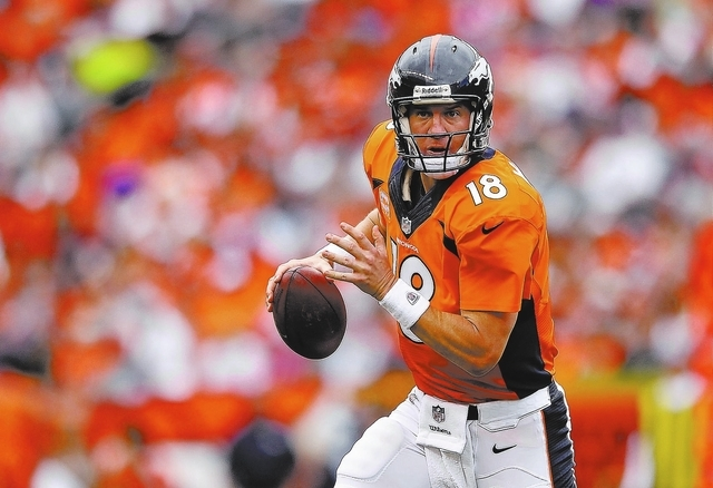 Denver Broncos quarterback Peyton Manning (18) rolls out of the pocket looking to pass against the Phildadelphia Eagles in the third quarter of an NFL football game, Sunday, Sept. 29, 2013, in Den ...