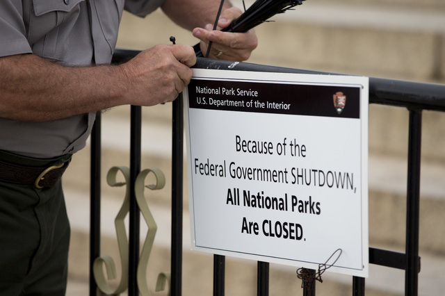 A National Park Service employee posts a sign on a barricade closing access to the Lincoln Memorial Tuesday in Washington. Congress plunged the nation into a partial government shutdown Tuesday as ...
