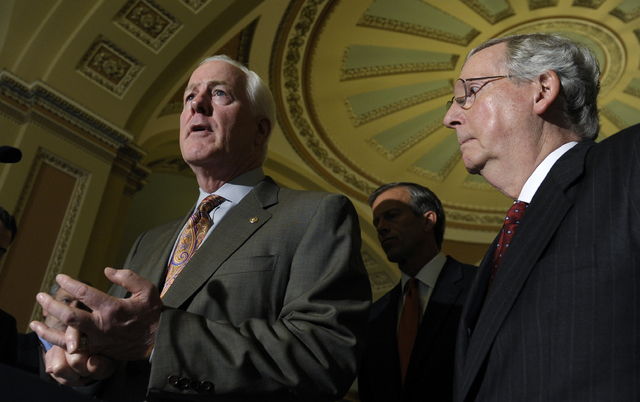 Senate Minority Leader Mitch McConnell of Ky., listens at right as Senate Minority Whip John Cornyn of Texas, left, speaks to reporters on Capitol Hill in Washington, Tuesday, Oct. 1, 2013, follow ...
