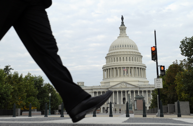 People walk near Capitol Hill in Washington, Tuesday, Oct. 1, 2013.  Congress plunged the nation into a partial government shutdown Tuesday as a long-running dispute over President Barack Obama's  ...
