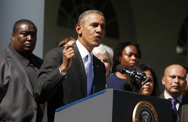 President Barack Obama stands with people who support the Affordable Care Act, his signature health care law, as he speaks in the Rose Garden of the White House in Washington, Tuesday, Oct. 1, 201 ...