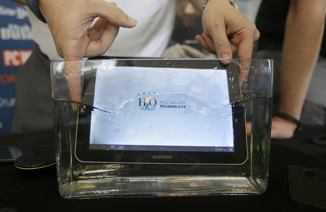 Steven Sherman, project management director for HZO, gives a demonstration of the HZO Waterblock Technology as he places a tablet into water at the GLAZED Conference, a conference for the business ...