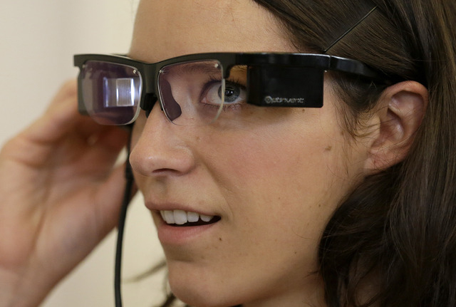 Claire Collins is given a demonstration of Optinvent ORA-S augmented reality glasses at the GLAZED Conference, a conference for the business of wearable technology, in San Francisco on Monday. The ...