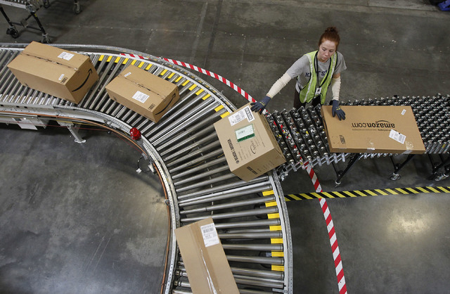 In this Nov. 11, 2010 file photo, Katherine Braun sorts packages toward the right shipping area at an Amazon.com fulfillment center in Goodyear, Ariz. Amazon.com said Tuesday, Oct. 1, 2013, it is  ...