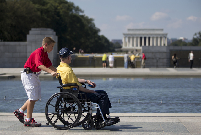 Korean War veteran Robert Olson, from Iowa, is pushed in his wheelchair by Zach Twedt, also from Iowa, around the National World War II Memorial in Washington, Tuesday, Oct. 1, 2013. Veterans who  ...