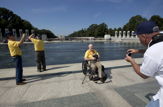 Korean War veteran Frederick Jenkins, from Iowa, third from left, poses for a photograph at National World War II Memorial in Washington, Tuesday, Oct. 1, 2013. Veterans who had traveled from acro ...