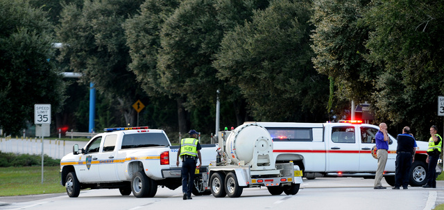 Police block the road to the Jacksonville International Airport terminal as the bomb disposal unit drives by on the right on Tuesday in Jacksonville, Fla. The airport was evacuated after authoriti ...