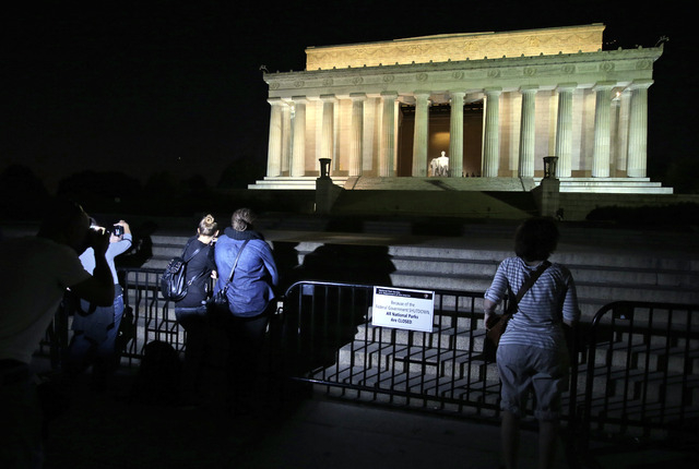 People take pictures in front of the steps of the closed Lincoln Memorial, Tuesday, Oct. 1, 2013, in Washington. The museums that draw millions of visitors to the National Mall closed their doors  ...