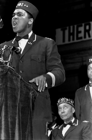 In this Feb. 25, 1968 file photo, former heavyweight boxing champion Muhammad Ali addresses a gathering at a Black Muslim convention in Chicago. Seated behind Ali is Elijah Muhammad, leader of the ...