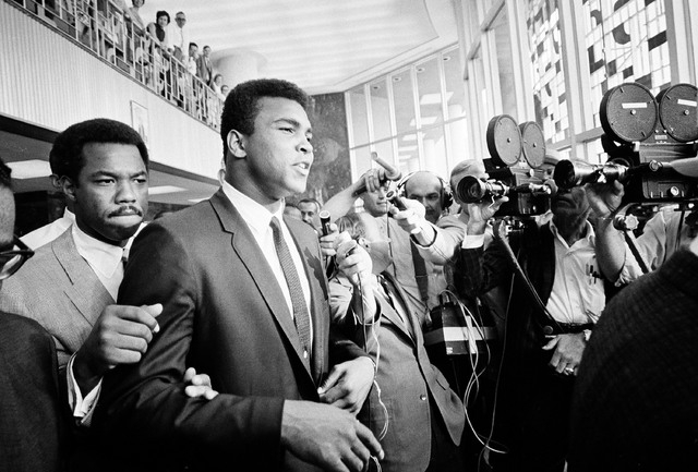 """In this June 19, 1967 file photo, heavyweight boxing champion Muhammad Ali has a """"no comment"""" as he is confronted by newsmen as he leaves the Federal Building in Houston during a recess in his tri ..."""