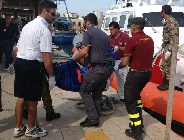 Firefighters unload the body of a drowned migrant from a Coast Guard boat in the port of Lampedusa, Sicily, Thursday. At least 94 people died when a ship carrying African migrants toward Italy cau ...
