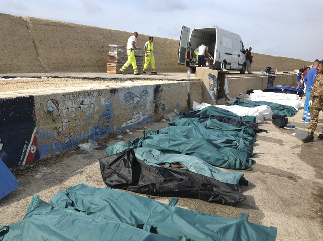 Bodies of drowned migrants are lined up in the port of Lampedusa Thursday, Oct. 3, 2013. Tens of people died when a ship carrying African migrants toward Italy caught fire and sank off the Sicilia ...