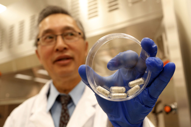 Dr. Thomas Louie, an infectious disease specialist at the University of Calgary, holds a container of stool pills in his lab in Calgary, Alberta, Canada, on Sept. 26. Half a million Americans get  ...
