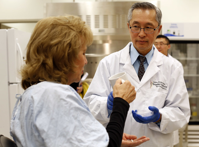 "Dr. Thomas Louie, right, an infectious disease specialist at the University of Calgary, administers fecal transplant pills to a patient in his lab. ""There's no stool left - just stool bugs. These  ..."