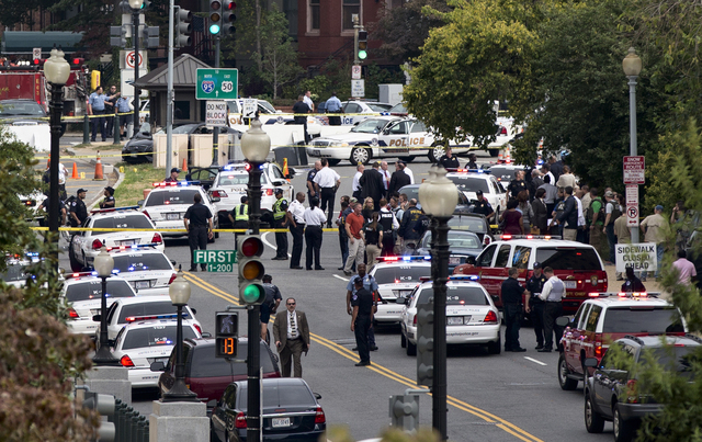 This view from the Russell Senate Office Building shows police converging on the scene of a shooting on Constitution Avenue on Capitol Hill near the Supreme Court in Washington on Thursday. A woma ...