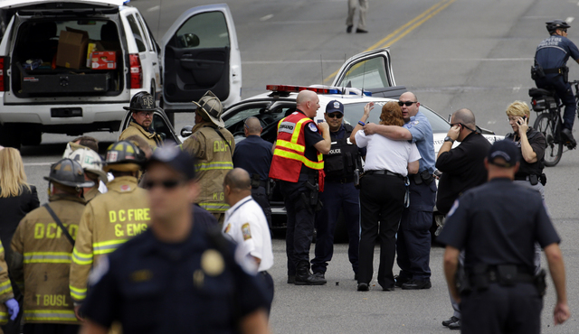 Police gather near the scene on Capitol Hill in Washington on Thursday after gunshots were heard. Police say the U.S. Capitol was put on a security lockdown amid reports of possible shots fired ou ...