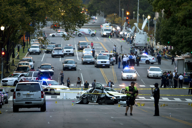 A damaged Capitol Hill police car is surrounded by crime scene tape on Constitution Avenue near the U.S. Capitol after a car chase and shooting Thursday in Washington. A woman with a young child i ...