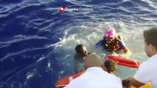 In this image made from video provided by the Italian Coast Guard and recorded on Thursday, Oct. 3, 2013, Italian Coast Guard rescue a survivor of a ship transporting hundreds of migrants which ca ...